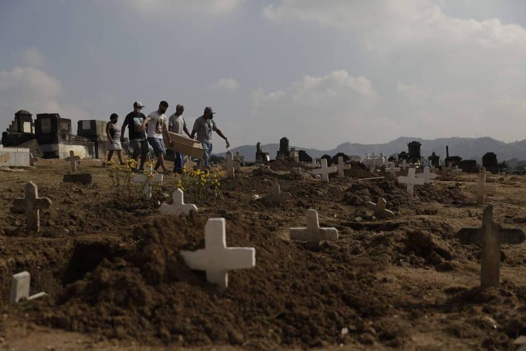 Marcos Vinicius Andrade da Silva, 26, enteado de Valnir, e outros carregam seu caixão no cemitério de Inhaúma