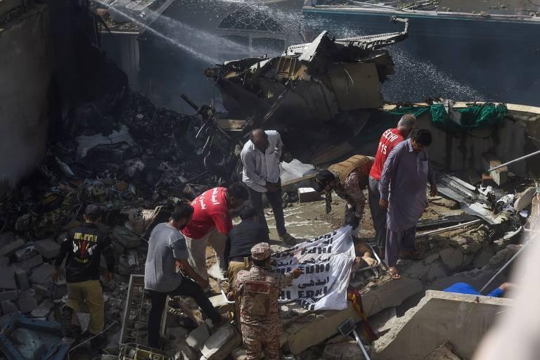 Membros de equipe de emergência cobrem corpo encontrado em destroços da aeronave da Pakistan International Airlines que caiu em área residencial em Karachi