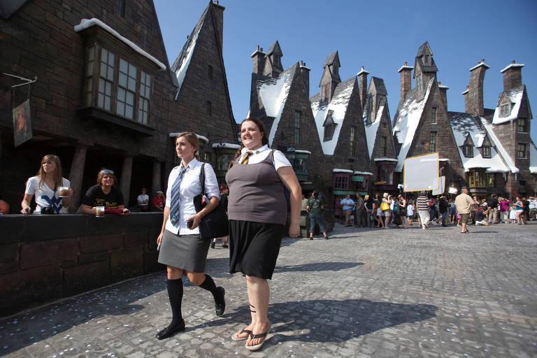 Duas mulheres caminham por vila cenográfica