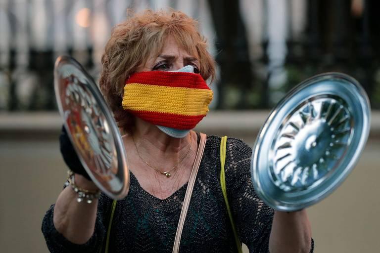 uma senhora, de cabelos curtos e loiros, com blusa preta e uma máscara nas cores da bandeira espanhola, vermelho e amarelo, bate duas tampas de panela