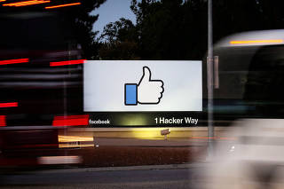 FILE PHOTO: The entrance sign to Facebook headquarters is seen through two moving buses in Menlo Park