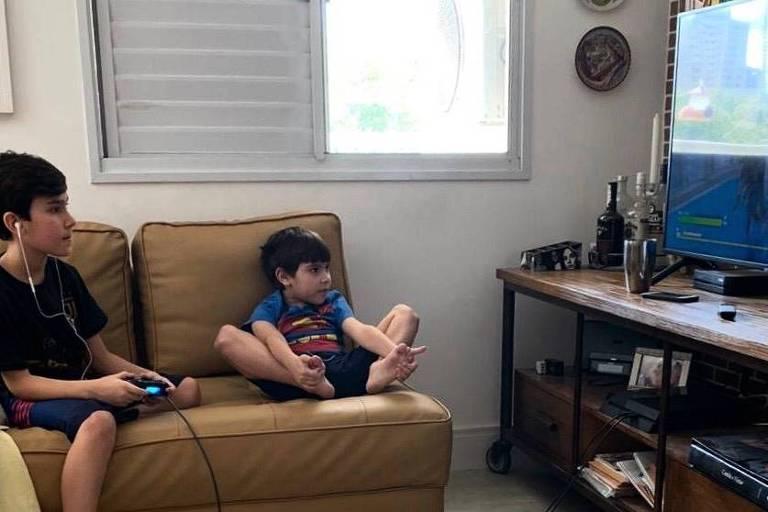 Dois meninos sentados no sofá na frente da televisão. O irmão mais velho segura o controle do console enquanto o mais novo assiste.