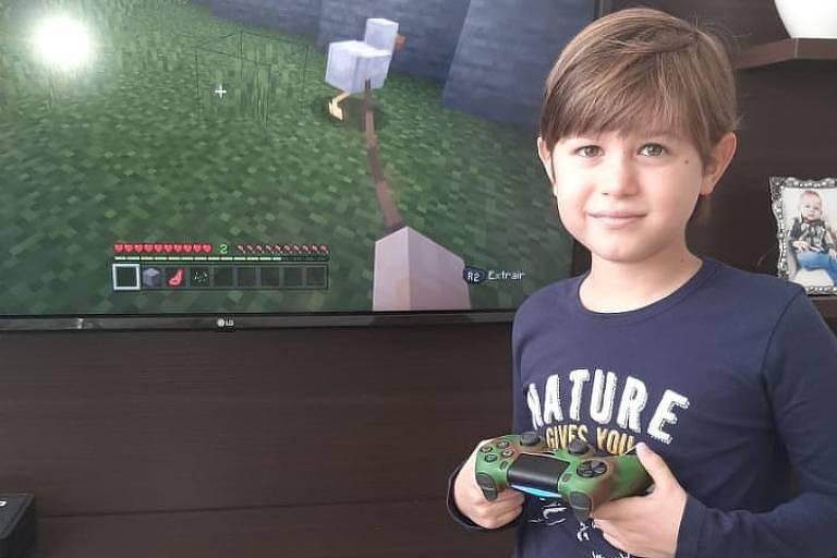 Menino veste pijama e está em pé, na frente da televisão, segurando o controle de um console