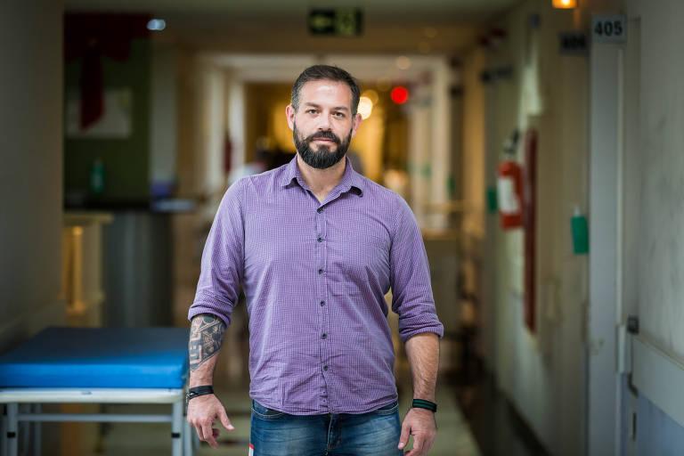 Em pé, em um corredor de hospital, o analista de sistemas Jacson Fressato, 37, criou o robô Laura que identifica pacientes com perfil para desenvolver sepse