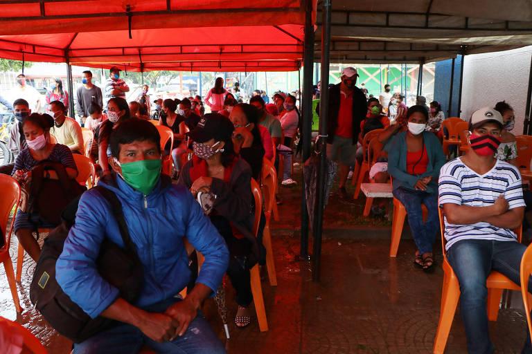 Indígenas aguardam atendimento em tenda improvisada em frente à Caixa Econômica Federal na manhã da quarta-feira (20) em Tabatinga (AM)