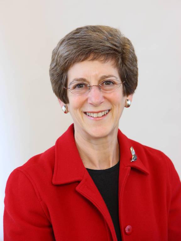 Barbara Mack sorri em foto em estúdio com fundo branco