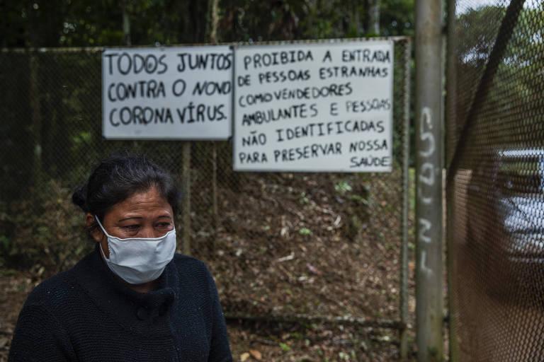 A educadora Janinha Gabriel ,42, chora em frente à entrada da aldeia, após saber que filho foi infectado