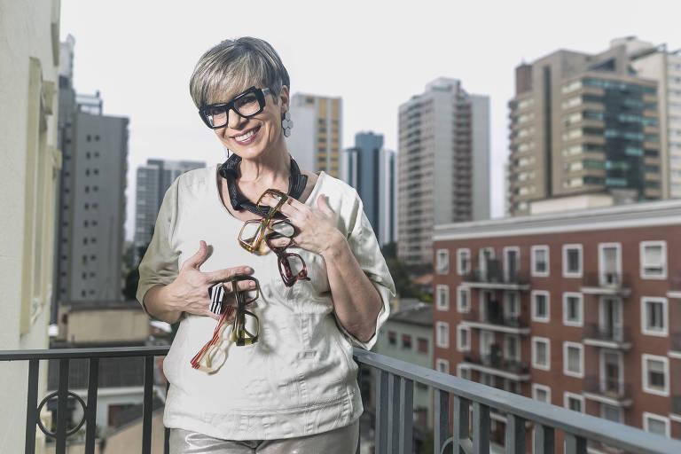 Mulher com cabelo curto e óculos em varanda segurando vários óculos nos braços