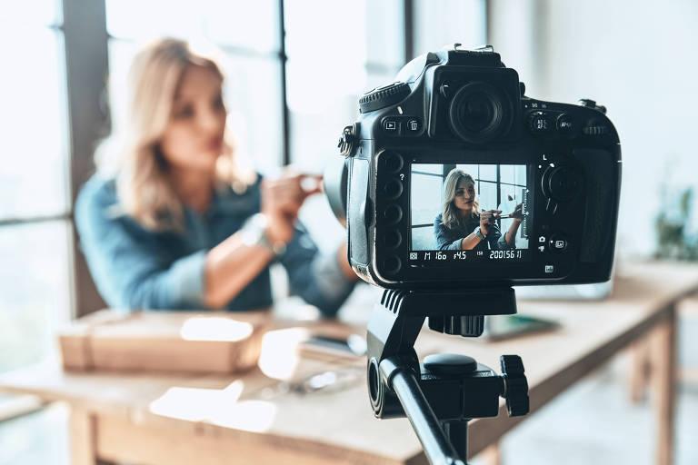 Mulher loira se filma fazendo algo em uma mesa