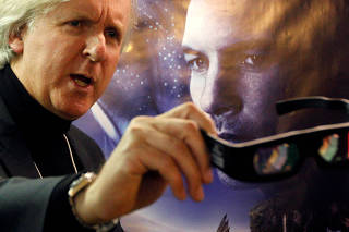 FILE PHOTO: Canadian director Cameron poses in front of a poster before a promotion event for his latest movie Avatar at the WEF in Davos