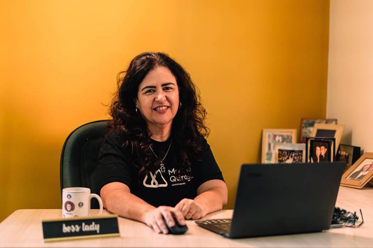 Marcela sentada em uma mesa de escritório, com um notebook, à frente de uma parede amarela