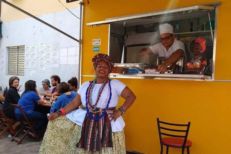 Teomila vestida de baiana em frente a trailer amarelo