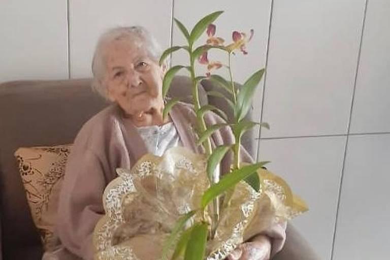 Maria da Mata Mussi, 94, diabética e com pressão alta, segurando uma flor. Ela se curou da Covid-19 depois de uma semana internada, em São José do Rio Preto (SP)