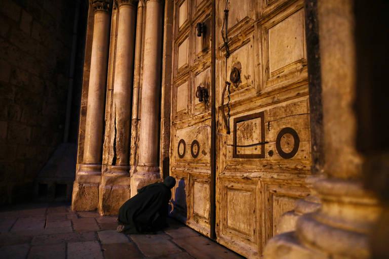 Fiel se ajoelha em frente à Basílica do Santo Sepulcro, em Jerusalém, que reabre neste domingo (24)