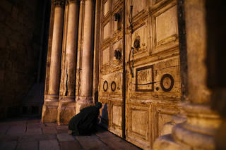 A worshipper kneels in front of the closed doors of the Church of the Holy Sepulchre remains shut due to coronavirus restrictions in Jerusalem's Old City