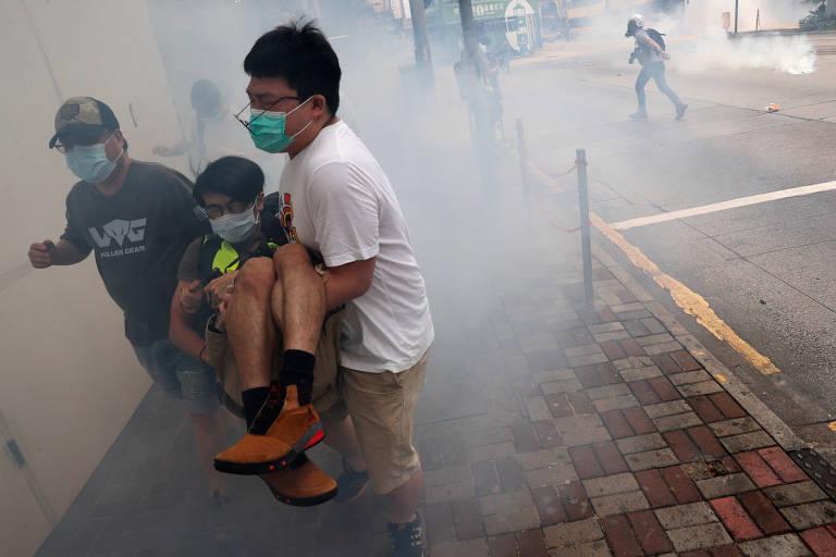 Manifestantes fogem após polícia atirar bombas de gás lacrimogêneo em Hong Kong