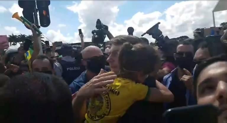 Presidente segura criança e é cercado por apoiadores