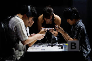 FILE PHOTO: Visitors try gaming program on Sony's Xperia smartphone at Tokyo Game Show 2019 in Chiba