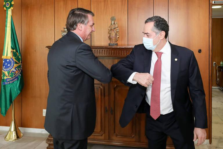 O presidente Jair Bolsonaro durante uma audiência com os ministro do Supremo Tribunal Federal Luís Roberto Barroso. Eles se cumprimentam com os cotovelos. Barroso está de máscara e Bolsonaro não