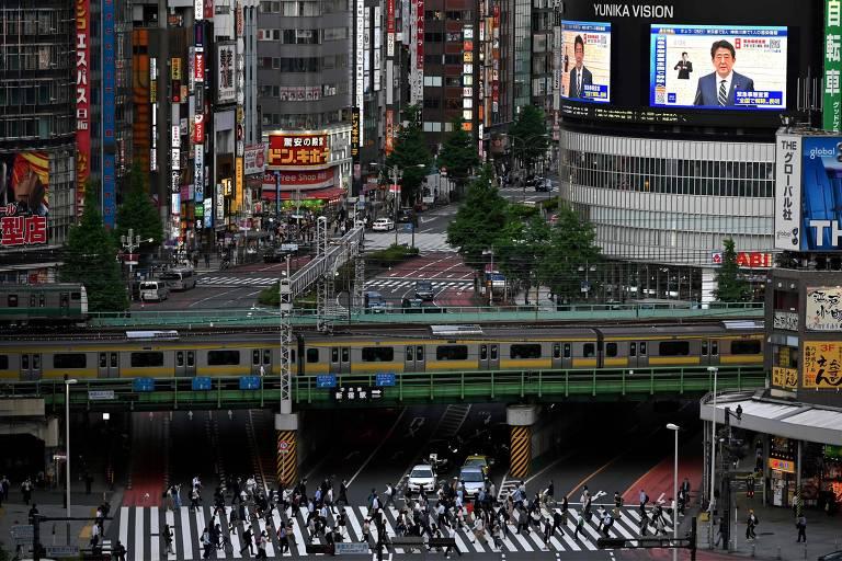 Telão mostra anúncio de primeiro-ministro japonês sobre rua movimentada