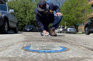 Chicago artist Jim Bachor creates four pandemic-themed pothole mosaics on the city's North Side