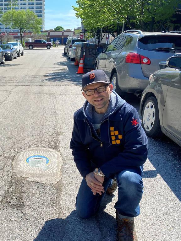 O artista de Chicago Jim Bachor cria quatro mosaicos nos buracos de rua com temas de pandemia no lado norte da cidade, durante o surto da doença por coronavírus (COVID-19) em Chicago, Illinois, EUA
