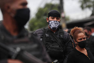 Police officers patrol the Alemao slums complex after an operation against drug gangs in Rio de Janeiro