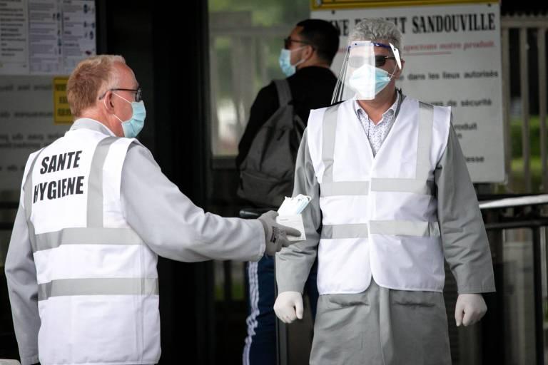 Agentes de saúde distribuem máscaras na entrada de fábrica na França