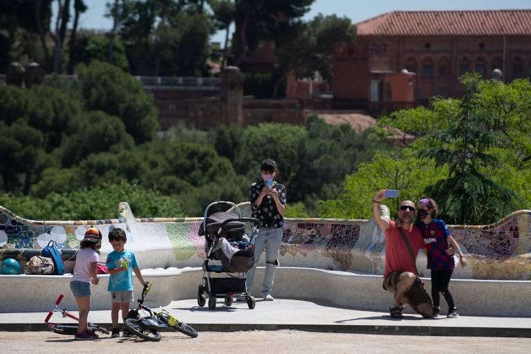 Crianças e adultos em parque, com chafariz ao fundo