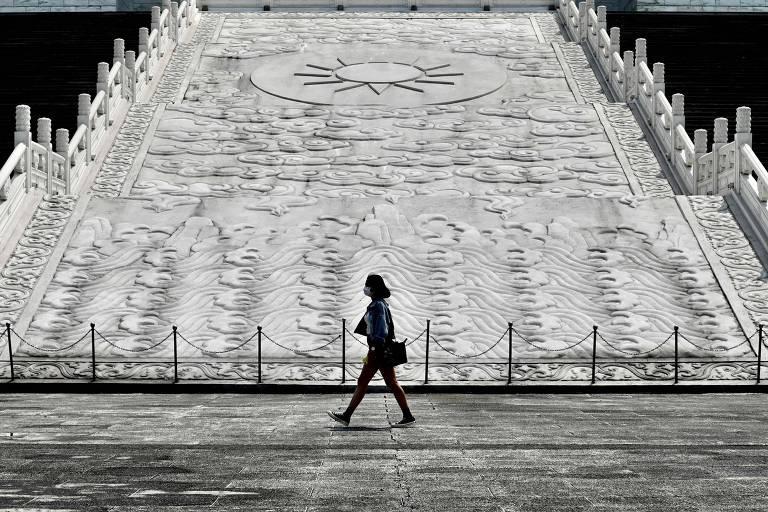 Mulher com máscara passa em frente a memorial em Taipei, em Taiwan