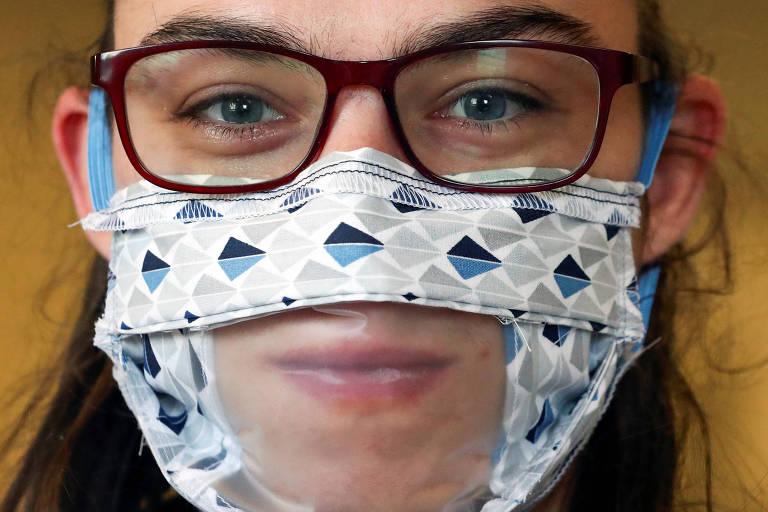 Funcionária da fábrica Brochage-Renaitre em Bruxelas, na Bélgica, usa máscara com recorte transparente para melhor se comunicar com colegas surdos