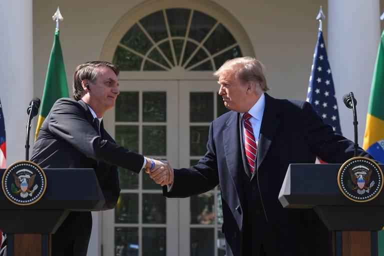Os presidentes de Brasil, Jair Bolsonaro, à esq., e EUA, Donald Trump, cumprimentam-se nos jardins da Casa Branca, em Washington