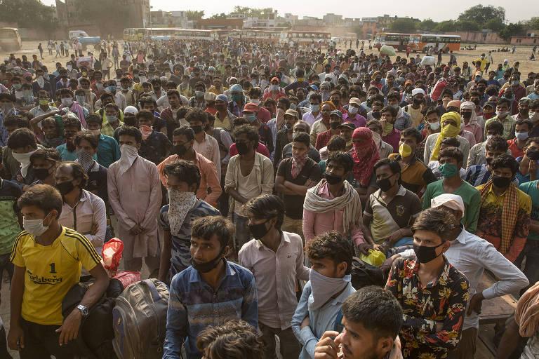 Dezenas de migrantes indianos aguardam em Ghaziabad, na região metropolitana de Déli, para tomarem ônibus de volta para suas cidades