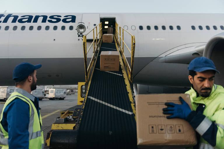 Dois homens com boné azul e colete amarelo carregam caixas em frente a avião com a porta aberta e uma esteira