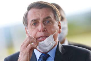 FILE PHOTO: Brazil's President Jair Bolsonaro adjusts his mask as he leaves Alvorada Palace, amid the coronavirus disease (COVID-19) outbreak in Brasilia