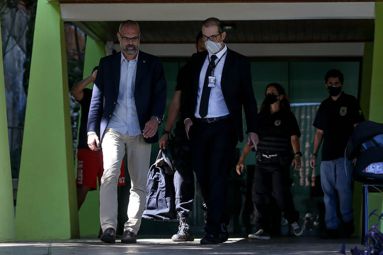 Blogueiro caminha ao lado de agente, que está de máscara de proteção, usa crachá e carrega uma sacola