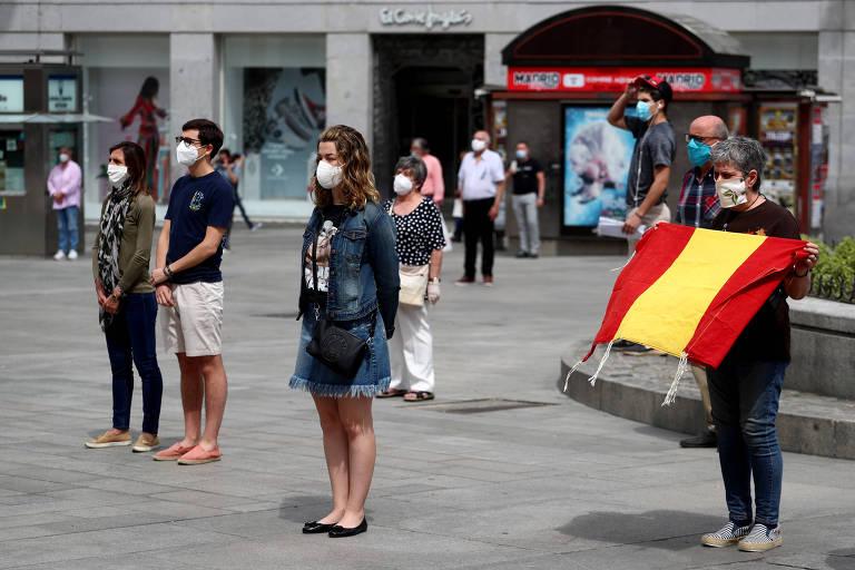 em uma praça, pessoas máscaras estão paradas. Uma delas segura uma bandeira com as cores da Espanha, vermelho e amarelo