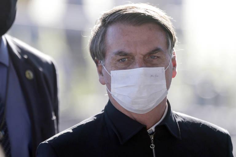 O presidente Jair Bolsonaro com máscara na porta do Palácio da Alvorada