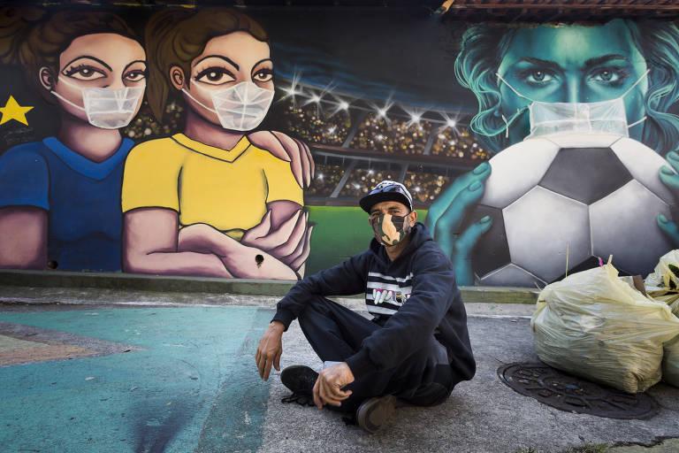 Digão, grafiteiro da Brasilândia, zona norte de São Paulo, coloca máscaras de plástico em seus trabalhos feitos na região, para conscientizar os moradores para o uso do equipamento de proteção