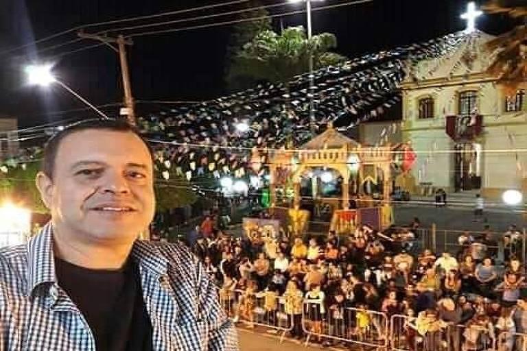 Homem em frente a igreja, onde ocorre uma festa