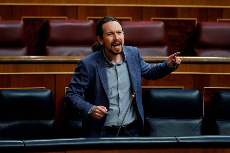 Pablo aparece de preto e camisa cinza, falando em um microfone e gesticulando com a mão enquanto discursa.