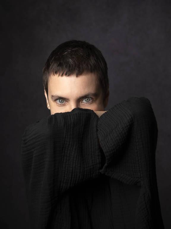 a cantora adriana calcanhotto esconde parte do rosto atrás de roupa preta