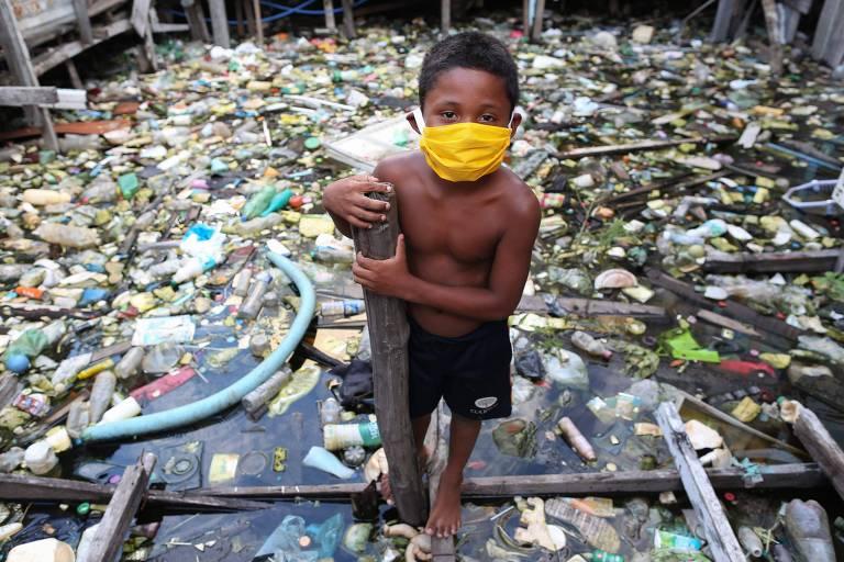 Menino sem camisa e de máscara amarela; atrás, lixo boiando na água