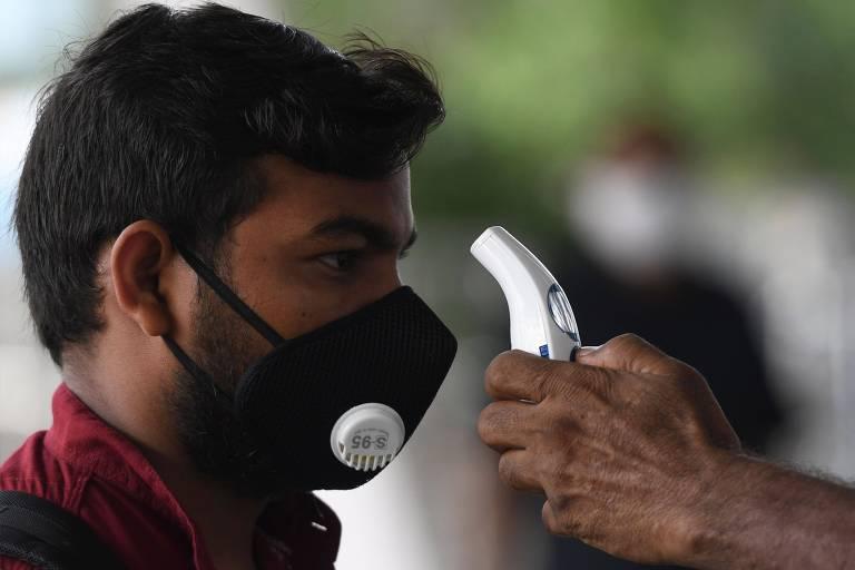 Homem indiano com máscara olha para frente enquanto tem temperatura medida por outra pessoa