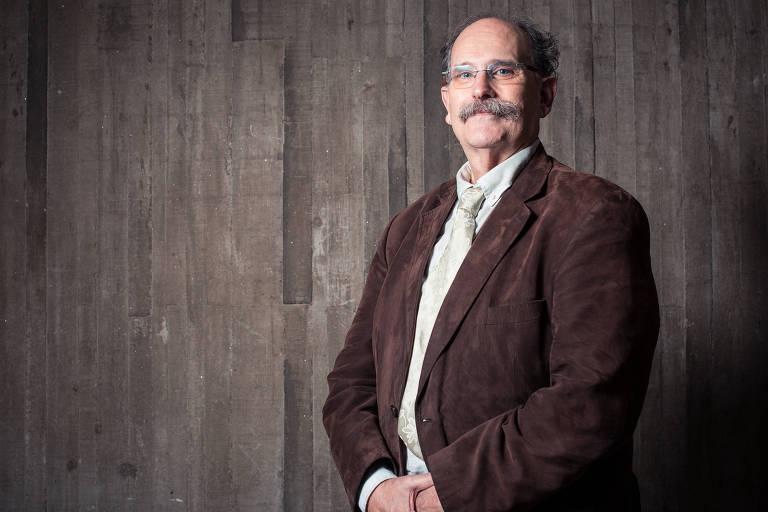 Homem calvo de bigode e óculos, com paletó marrom escuro, gravata e camisa clara.