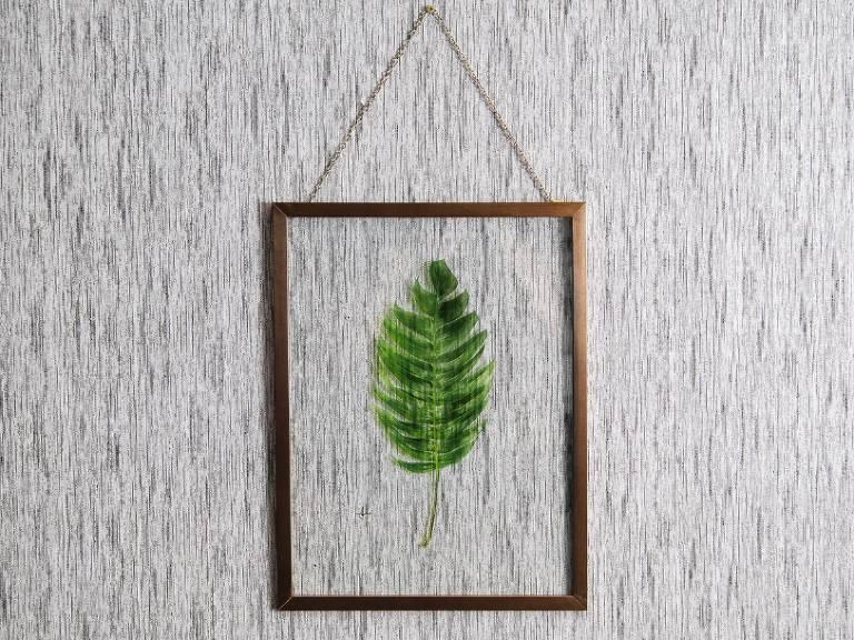 Quadro com uma folha pendurado em uma parede cinza