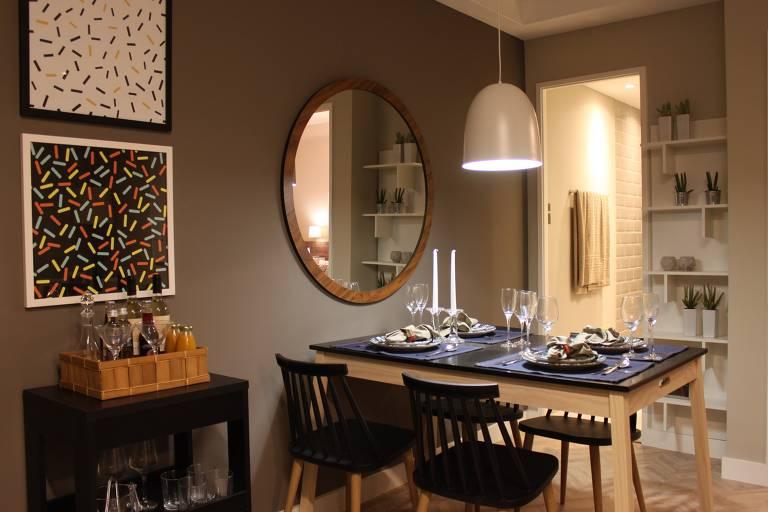 Ambiente com mesa de jantar com cadeiras de encosto vazado. Acima dela, um espelho redondo na parede