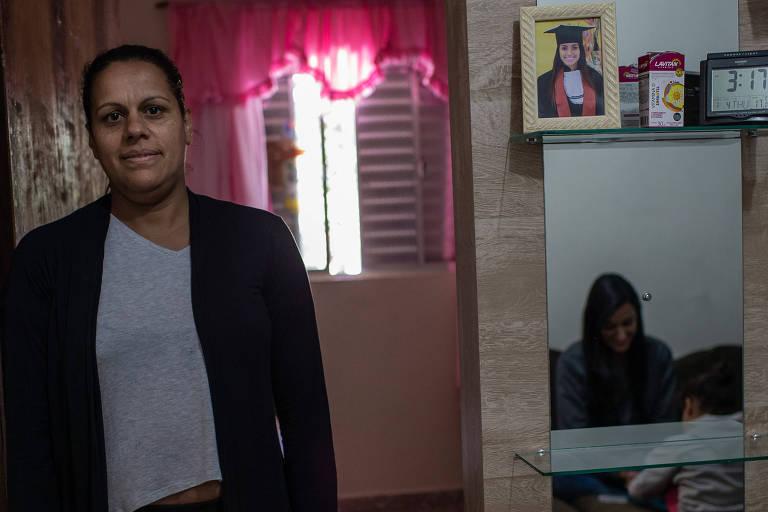 Celma na sala de casa, com as filhas refletidas no espelho