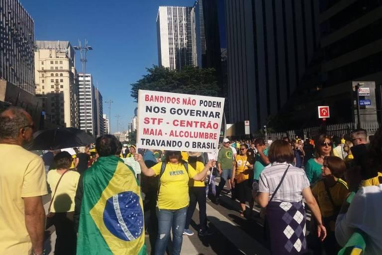 Manifestante pró-governo exibe cartaz com repúdio ao centrão durante ato na avenida Paulista