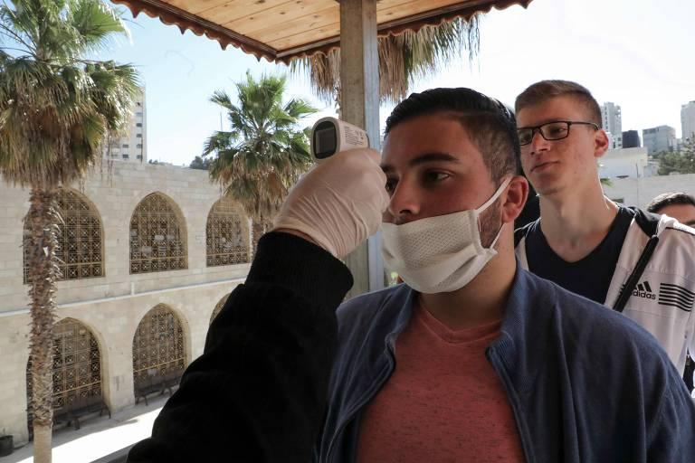 Mão com luva segura termômetro de distância frente a jovem com máscara cirúrgica